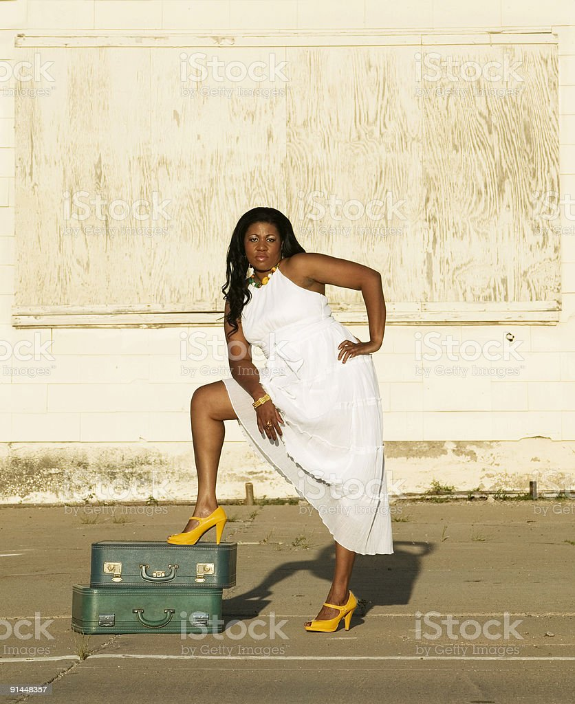 African American woman with foot on suitcases royalty-free stock photo