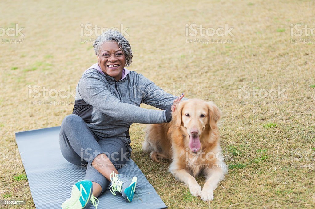 African American woman with pet dog sitting outdoors stock photo