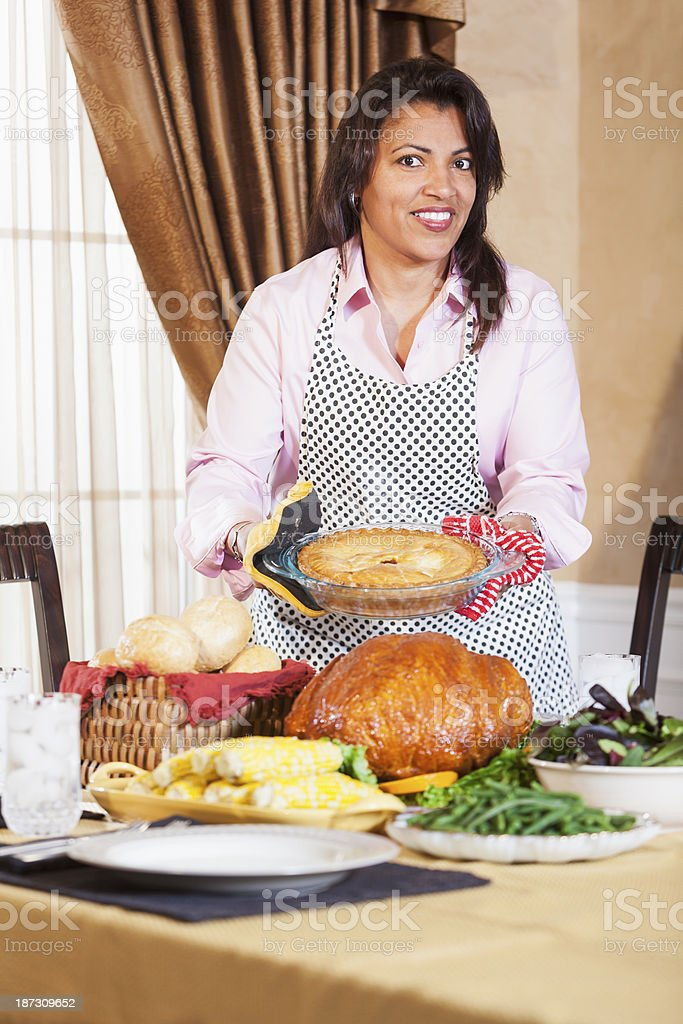 African American woman with traditional holiday meal on table stock photo