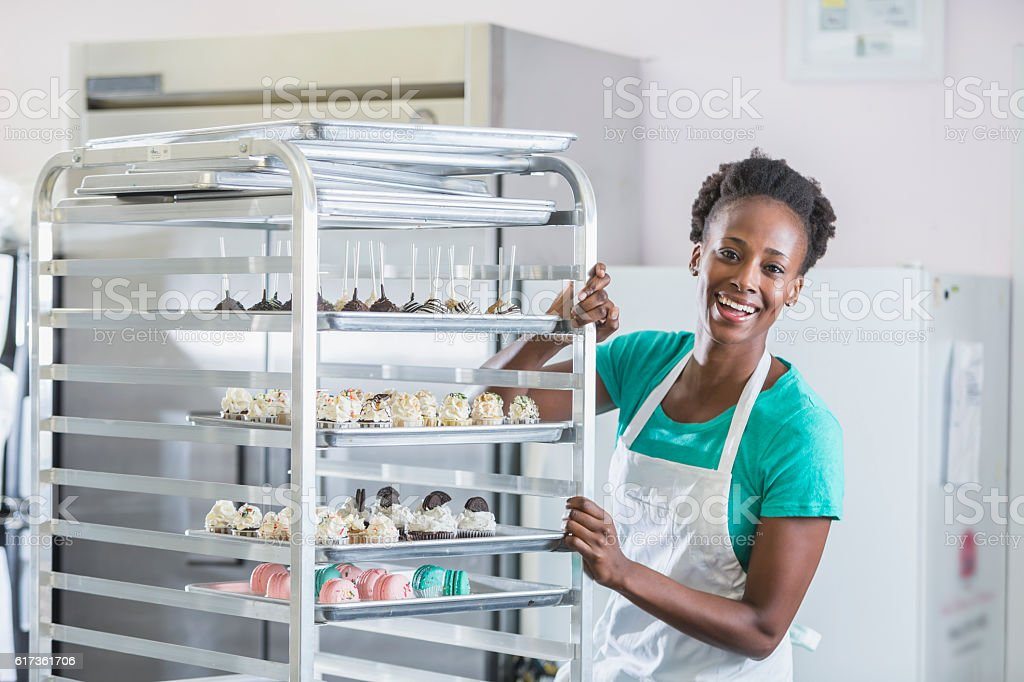 African American woman working in bakery kitchen stock photo