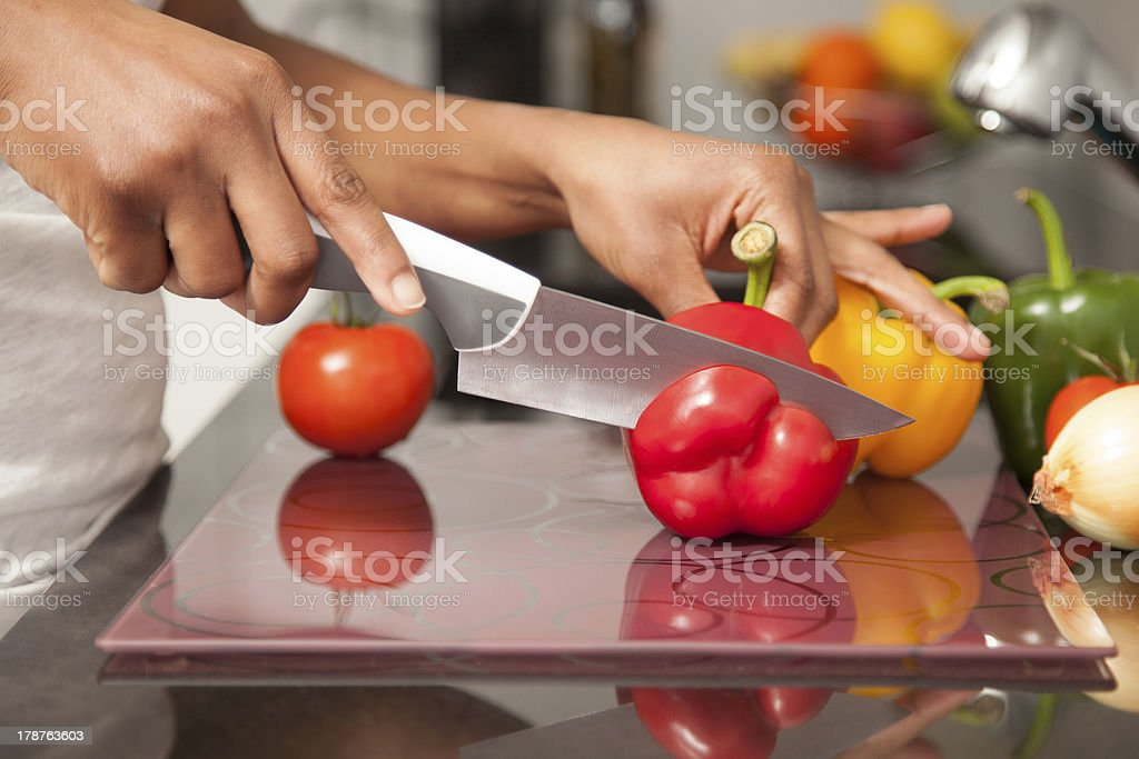 African  American womans hand slicing a red pepper stock photo