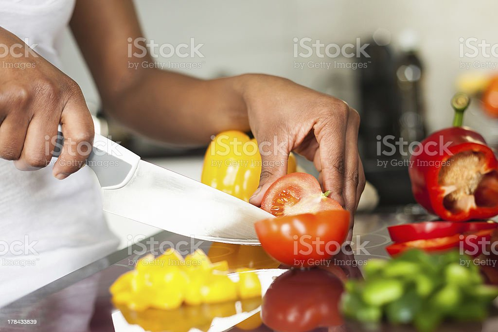 African  American womans hand slicing a tomatoe stock photo