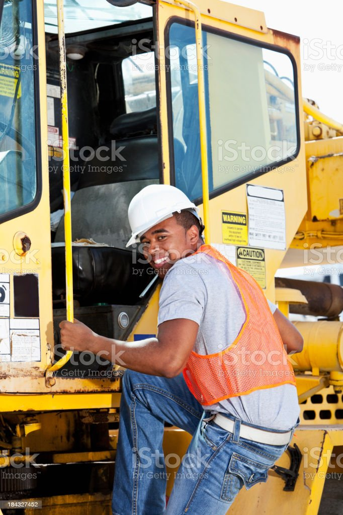 African American worker climbing onto a crane stock photo