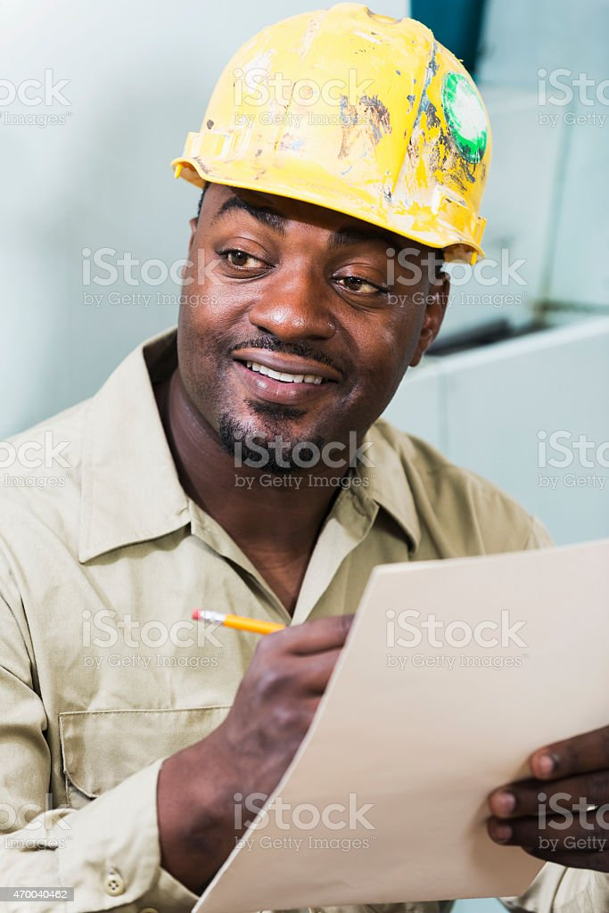 African American worker in hardhat, writing stock photo