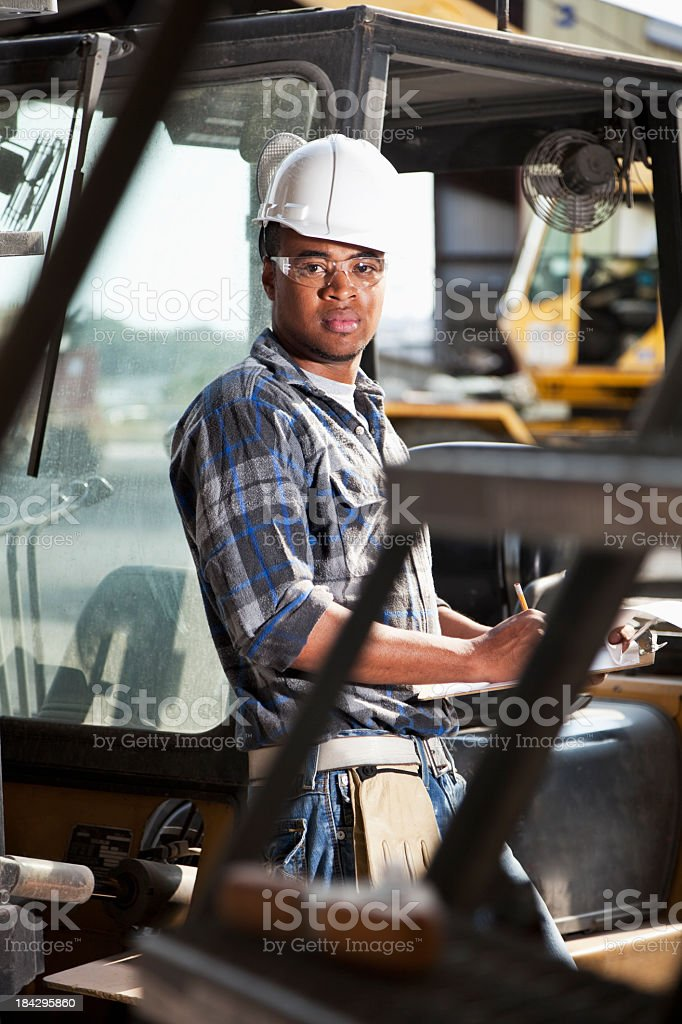 African American worker leaning on forklift royalty-free stock photo