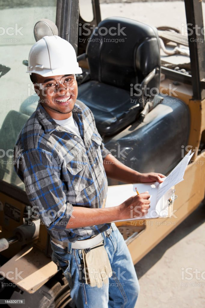 African American worker leaning on forklift stock photo