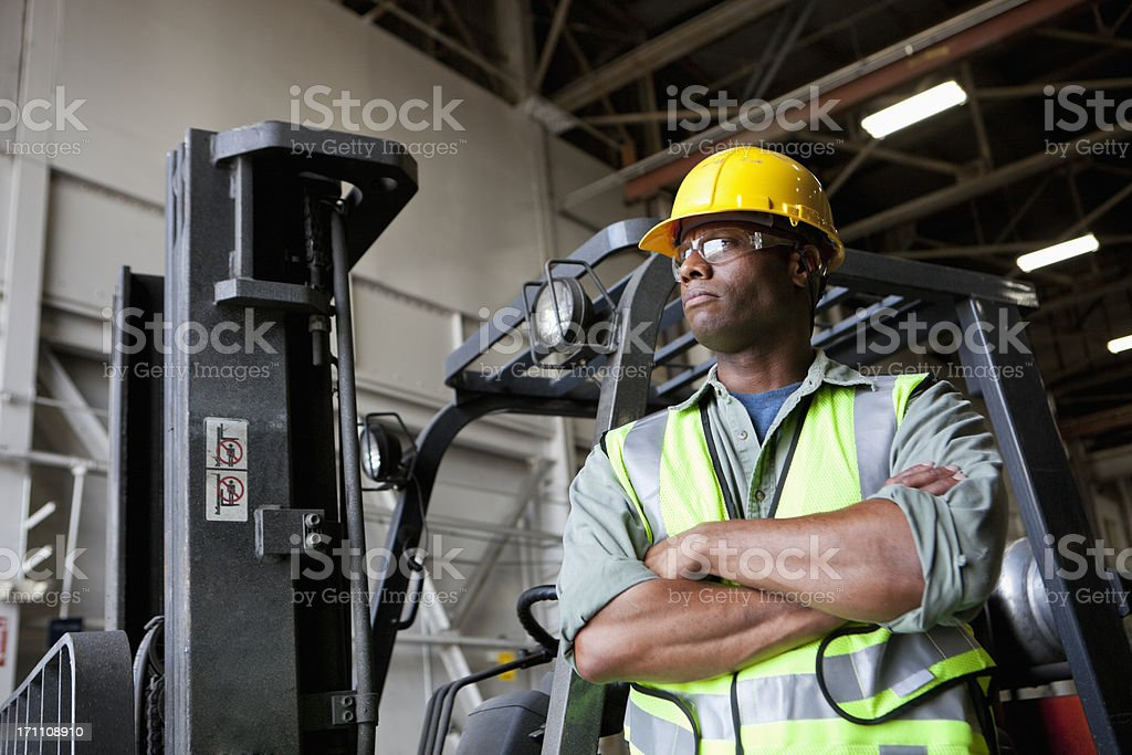 African American worker standing beside forklift royalty-free stock photo