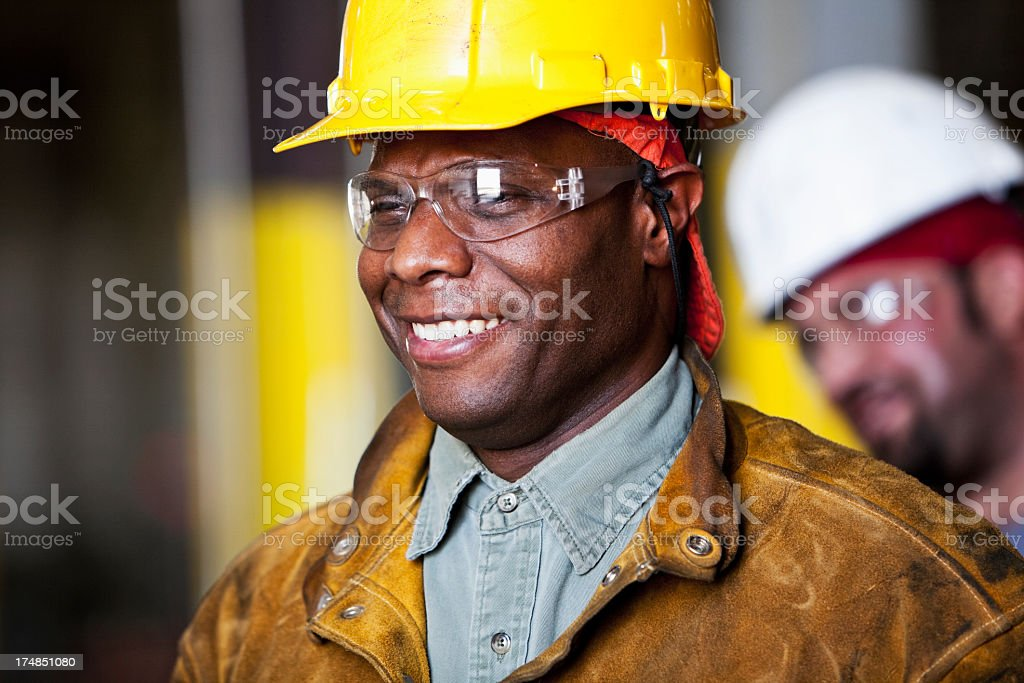 African American worker wearing safety glasses and hard hat stock photo
