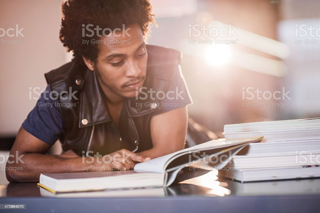 African American young man reading a book and studying. stock photo
