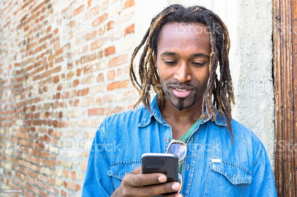 African american young man using mobile smart phone stock photo