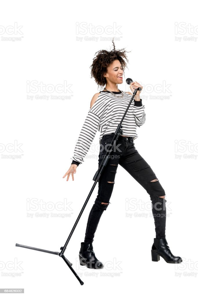 african american young woman singing with microphone isolated on white, female singer with microphone concept stock photo
