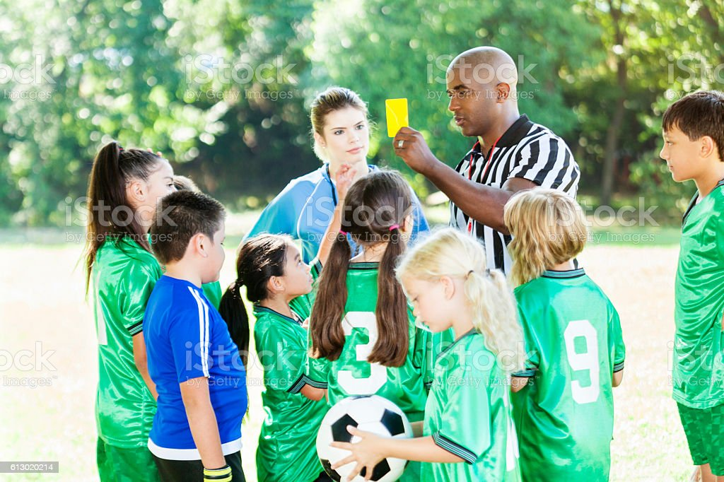 African American youth soccer referee explains penalty to teams stock photo