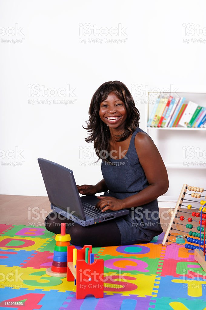 African AmericanWoman On  Mat Smiling And Using A Laptop stock photo