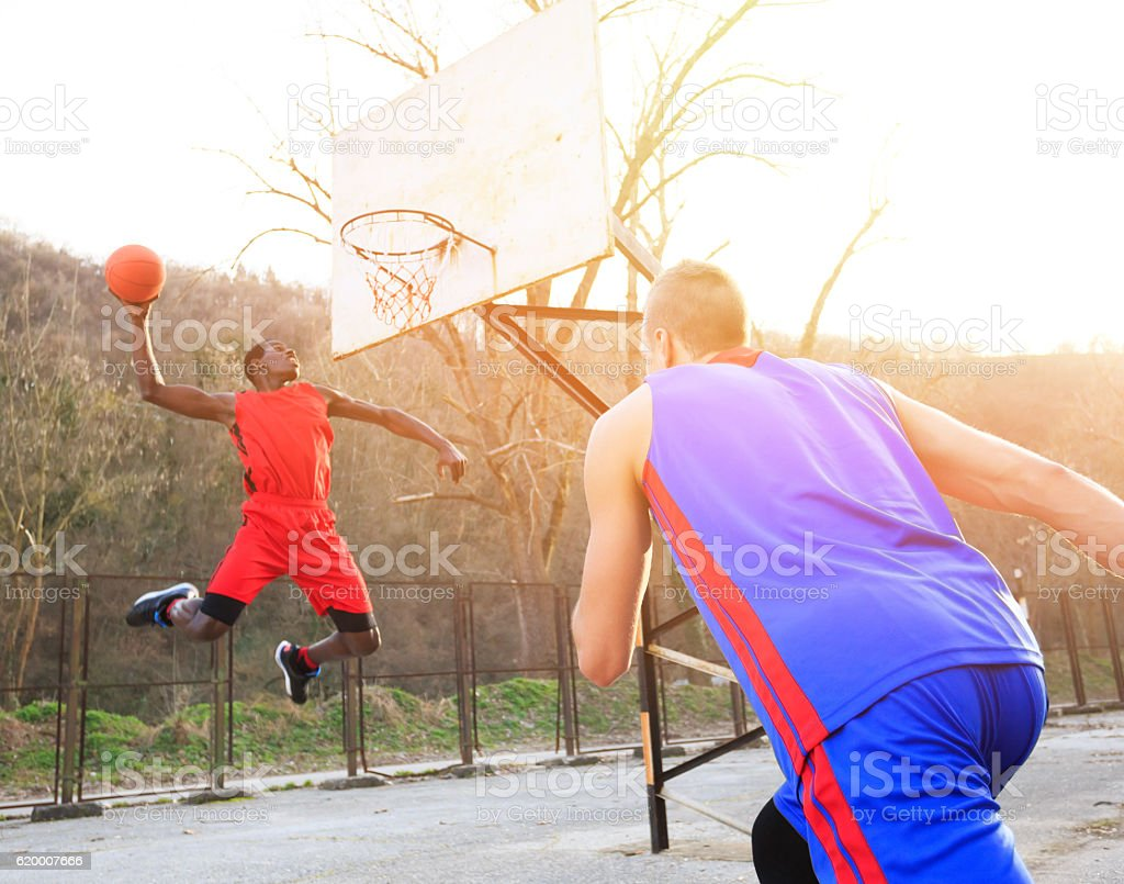 African basketball player slam dunking stock photo