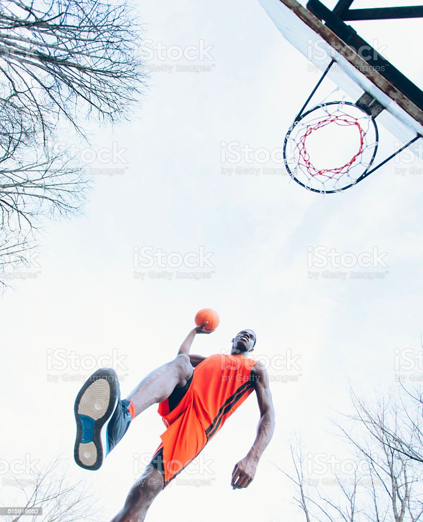African basketball player taking a shot to the hoop stock photo