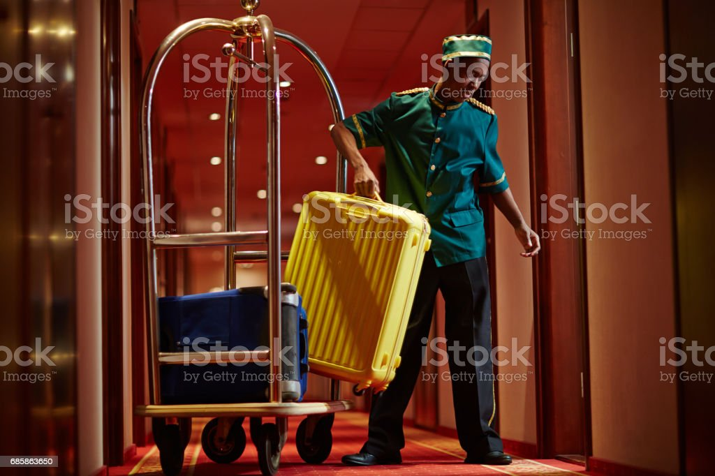 African Bellboy Delivering Luggage to Hotel Rooms stock photo