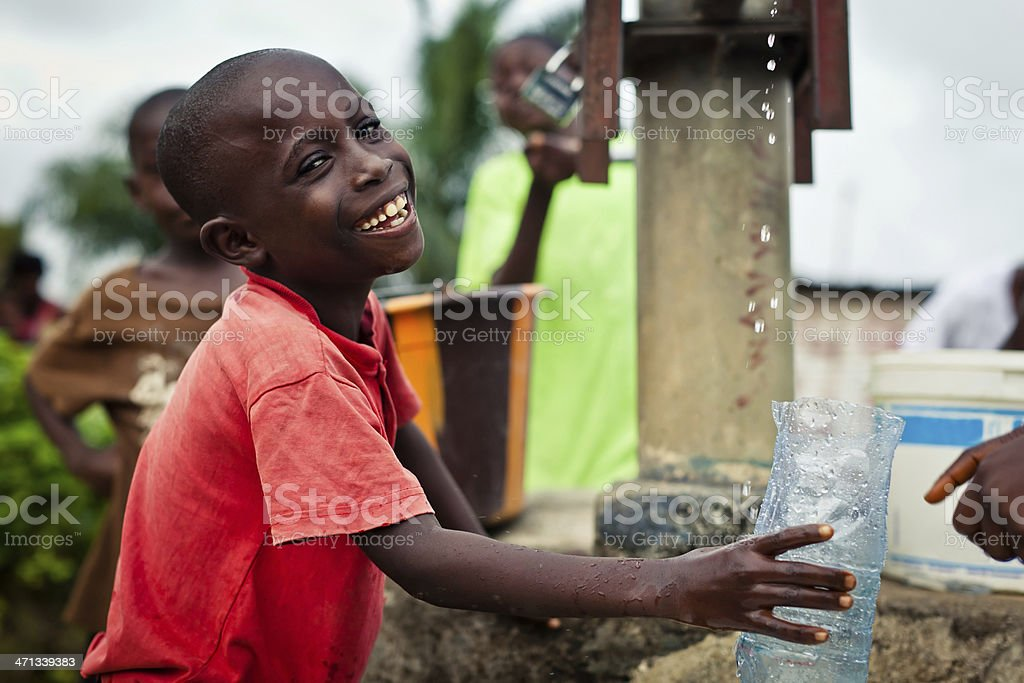 African Boy By Water Pump stock photo