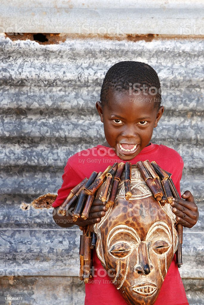African boy holding tribal mask royalty-free stock photo