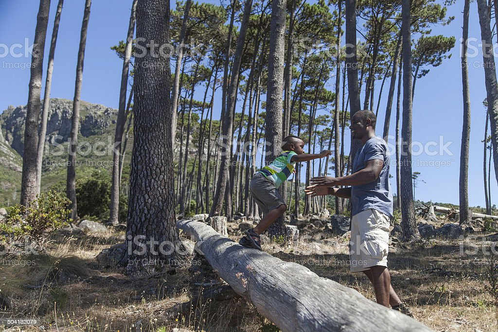 African boy jumping off a log into his fathers arms royalty-free stock photo