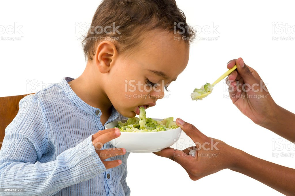 African boy refusing his vegetables stock photo