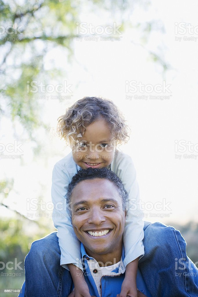 African boy sitting on fathers shoulders royalty-free stock photo