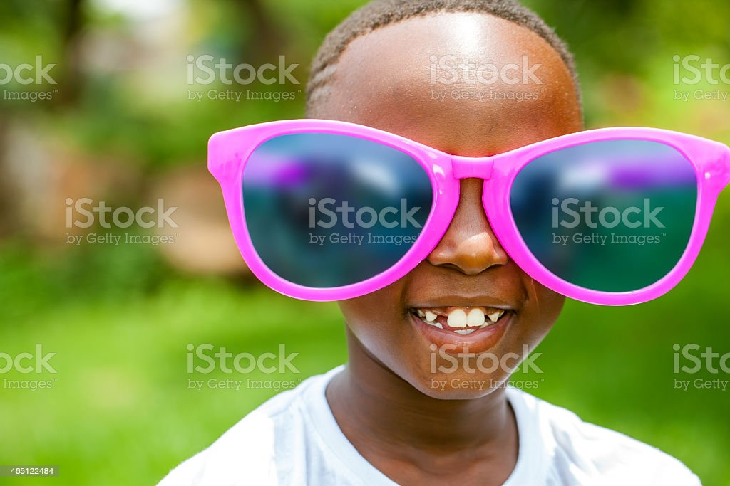 African boy wearing fun extra large sun glasses. stock photo