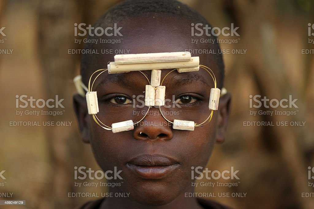 African boy with makeshift wooden glasses stock photo