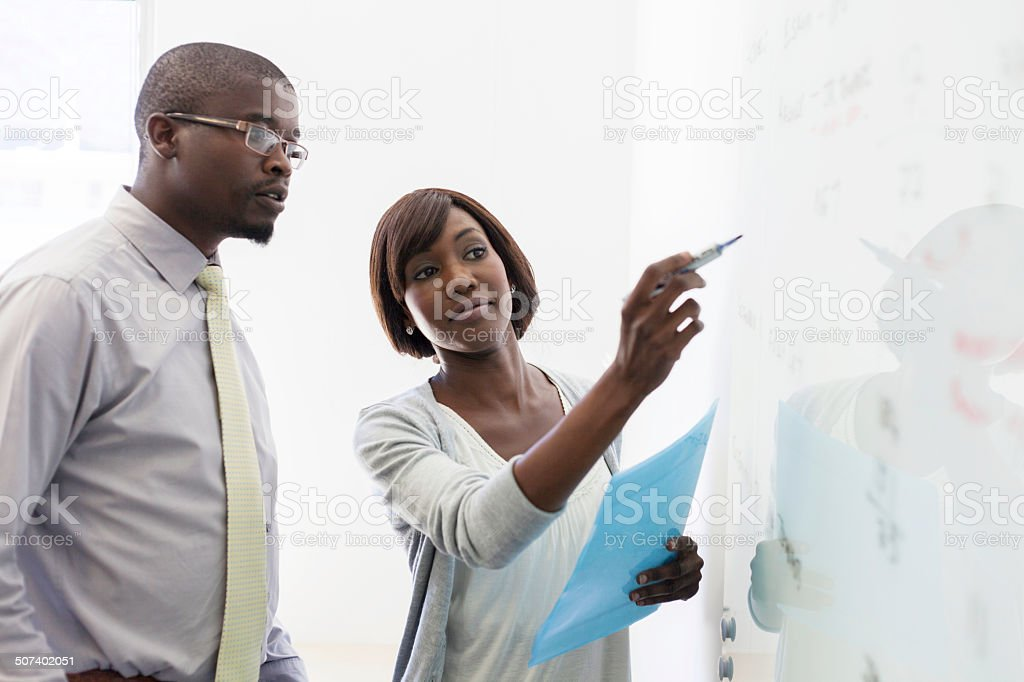 African business colleagues writing on the whiteboard stock photo