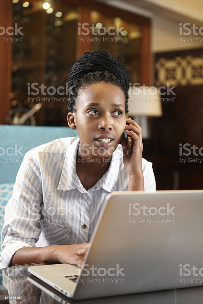 African Business woman taking a call while she works late stock photo