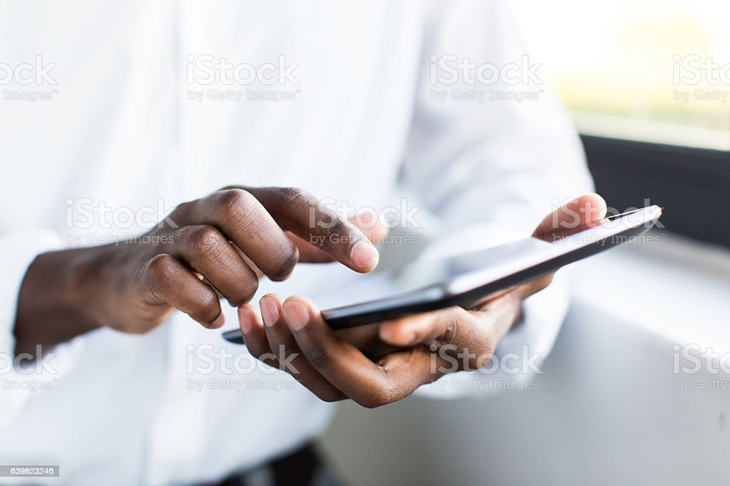 African businessman holding a digital tablet. stock photo