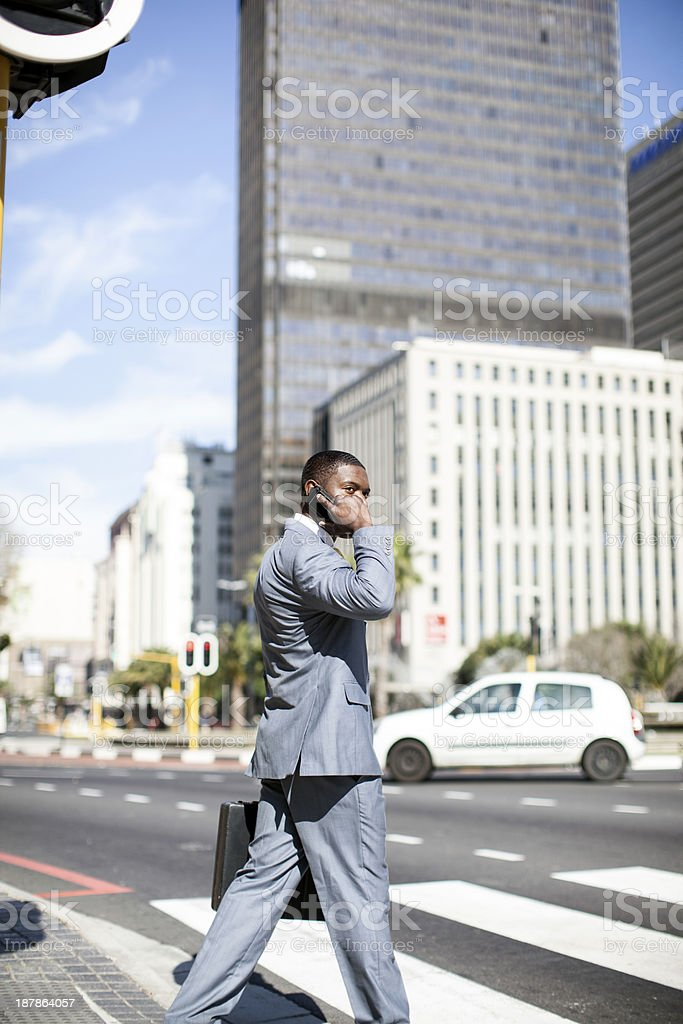 African businessman on his mobile phone, crossing the road. royalty-free stock photo