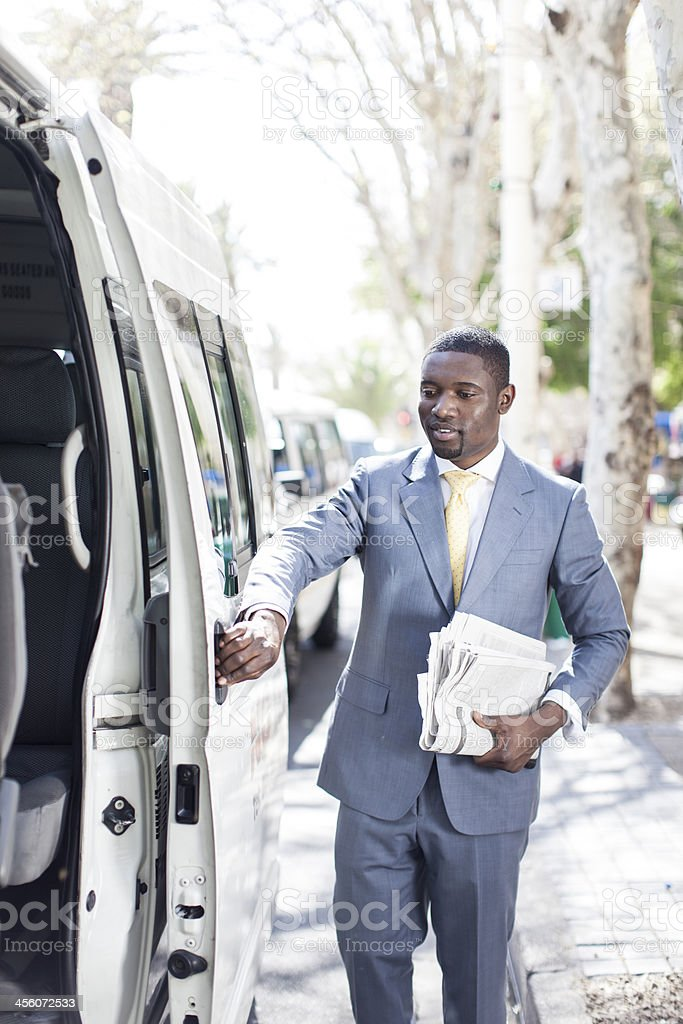 African businessman opening the doors of a taxi stock photo