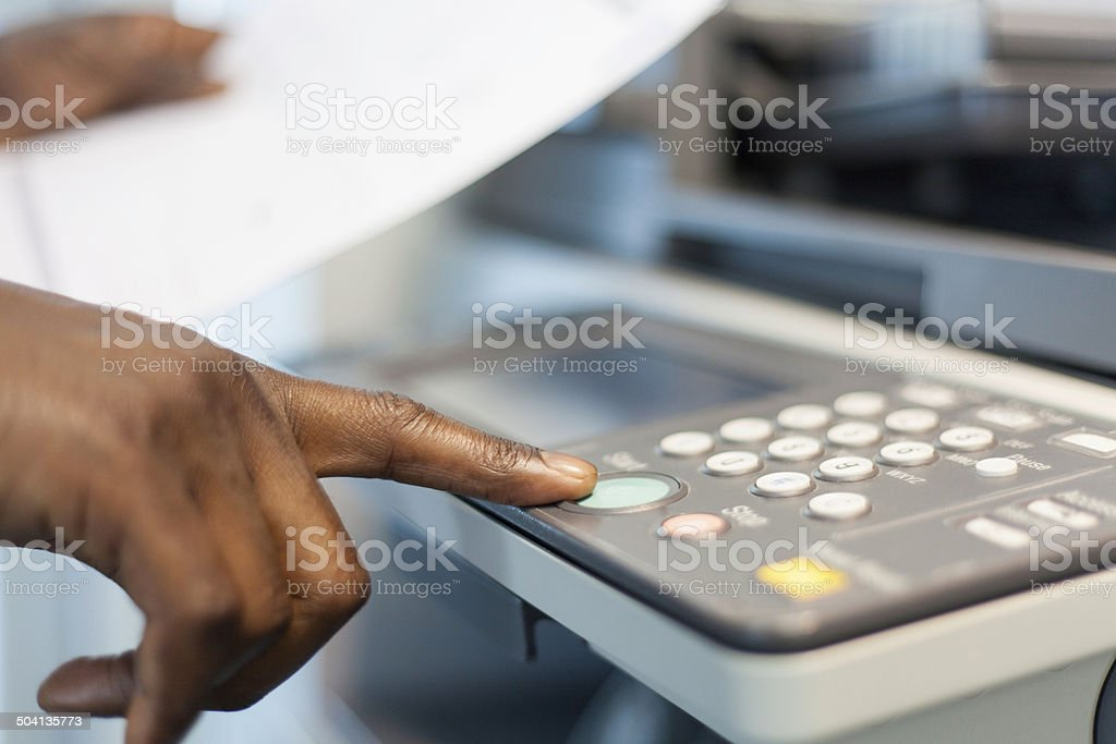 African businessman pressing the start button to print. stock photo