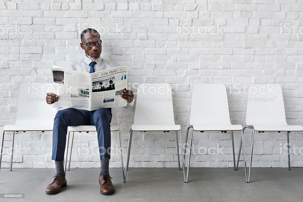 African Businessman Reading Newspaper Workplace Concept stock photo