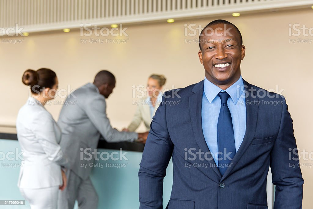 african businessman standing at hotel reception stock photo