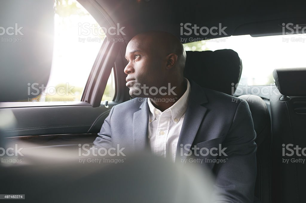 African businessman traveling to work in the luxury car stock photo