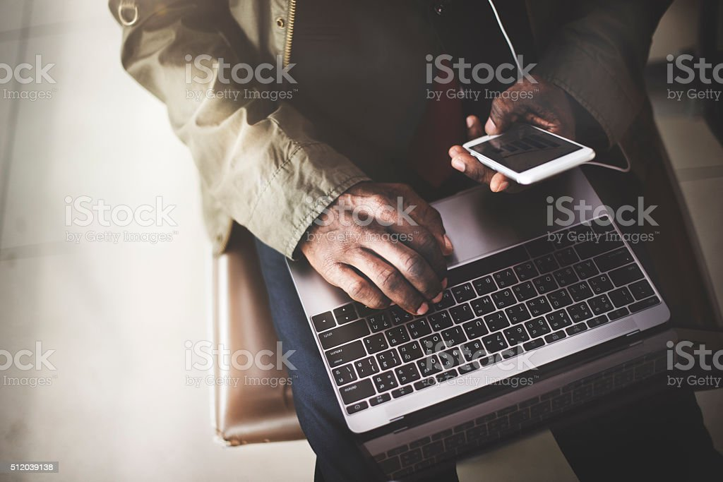 African Businessman Using Digital Laptop Smart Phone Concept stock photo