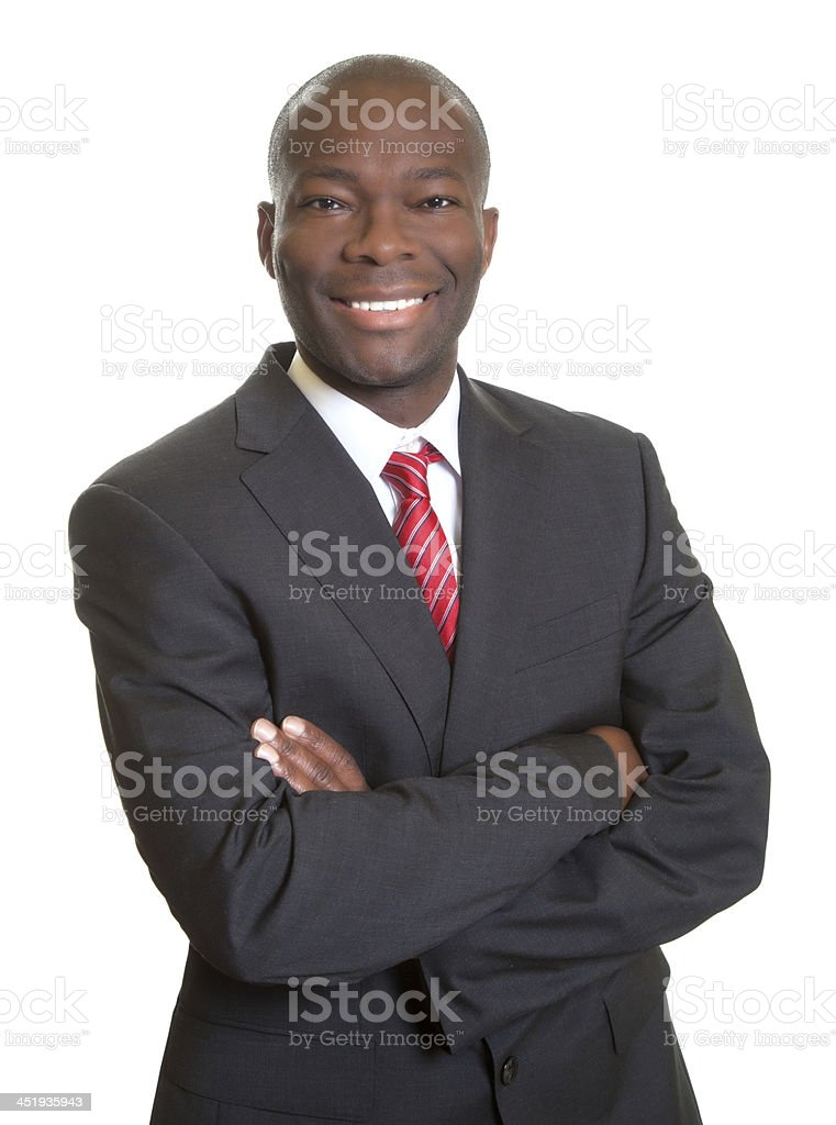 African businessman with crossed arms laughing at camera stock photo