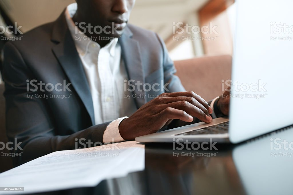 African businessman working on laptop at cafe stock photo