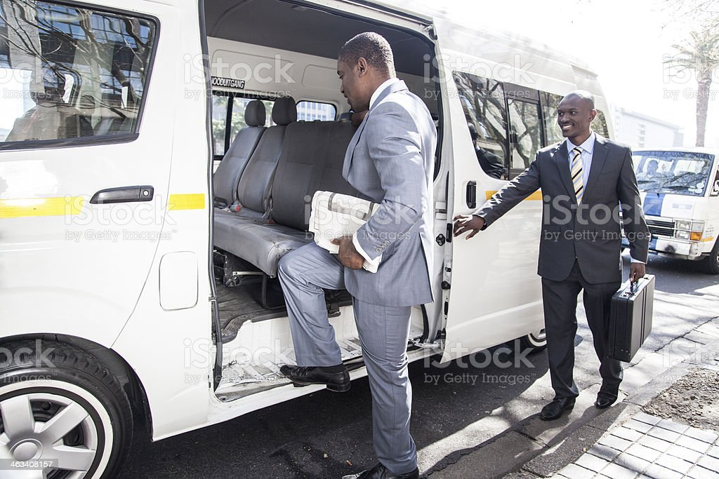 African businessmen getting in a taxi stock photo