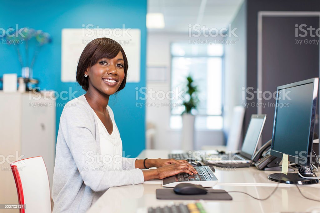 African businesswoman busy typing on her computer stock photo