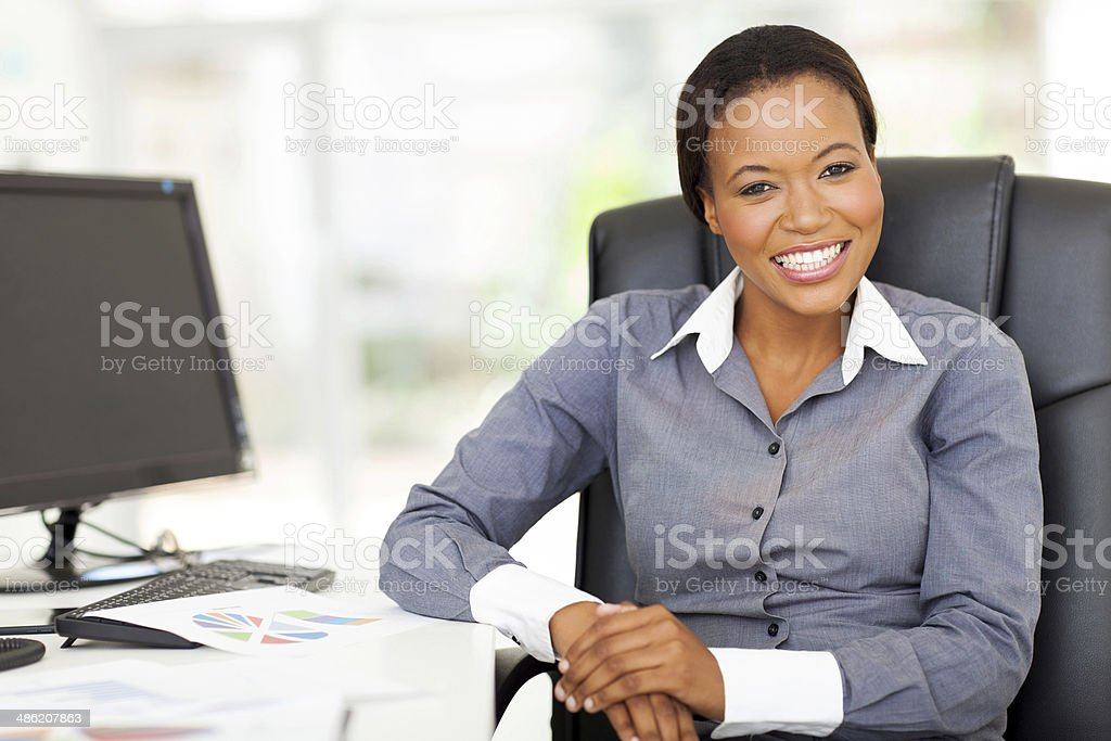 african businesswoman sitting in office stock photo