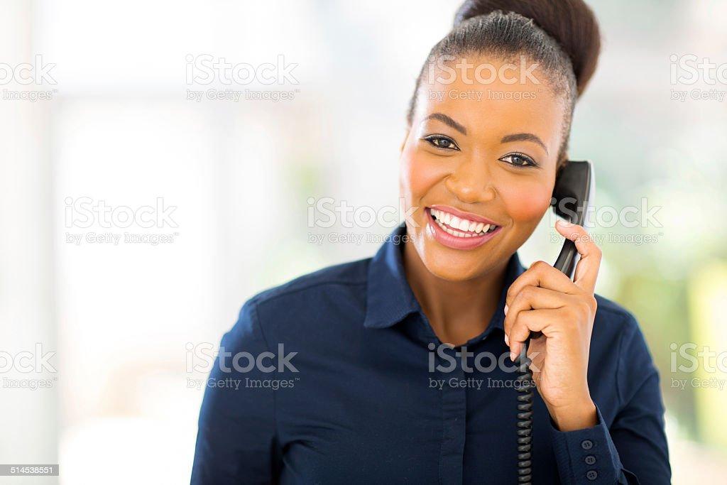 african businesswoman using landline phone stock photo