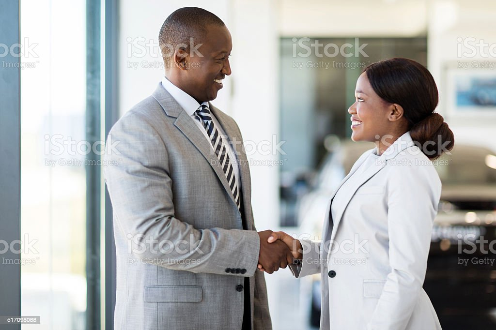 african car dealer handshake with customer stock photo