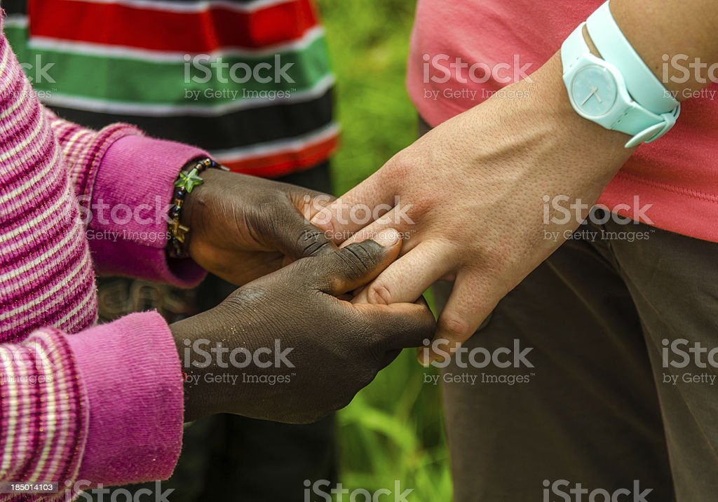 African Child holds a White Hand royalty-free stock photo