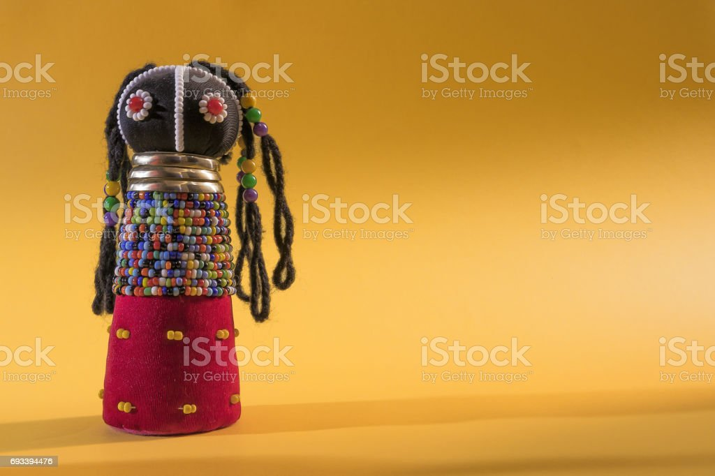 African cloth doll isolated on yellow background stock photo
