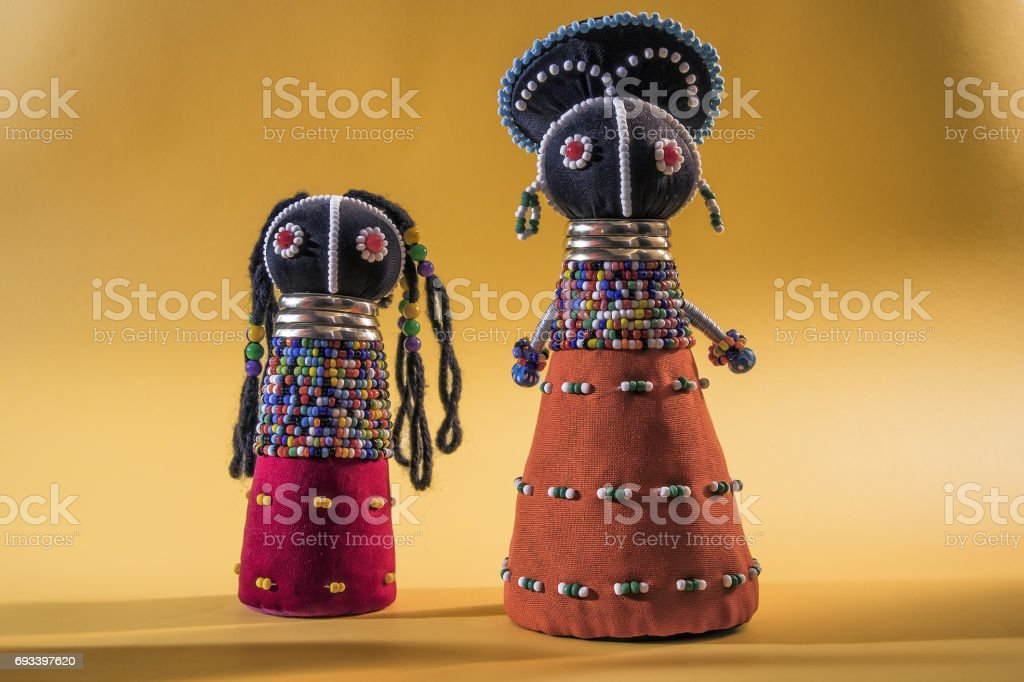 African cloth dolls isolated on yellow background stock photo
