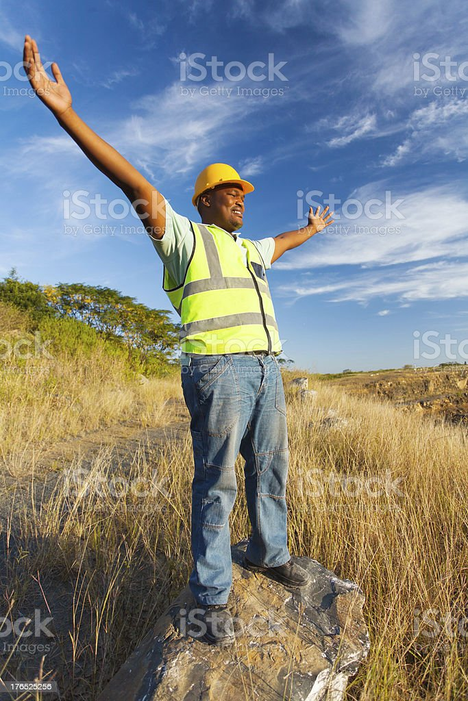african construction worker with arms outstretched royalty-free stock photo