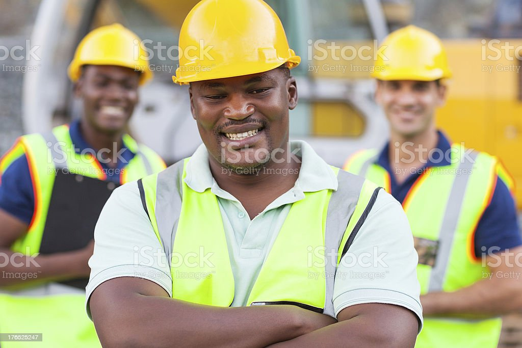 african construction worker with colleagues royalty-free stock photo