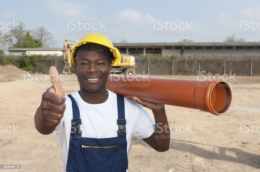 African construction worker with pipe showing thumb stock photo
